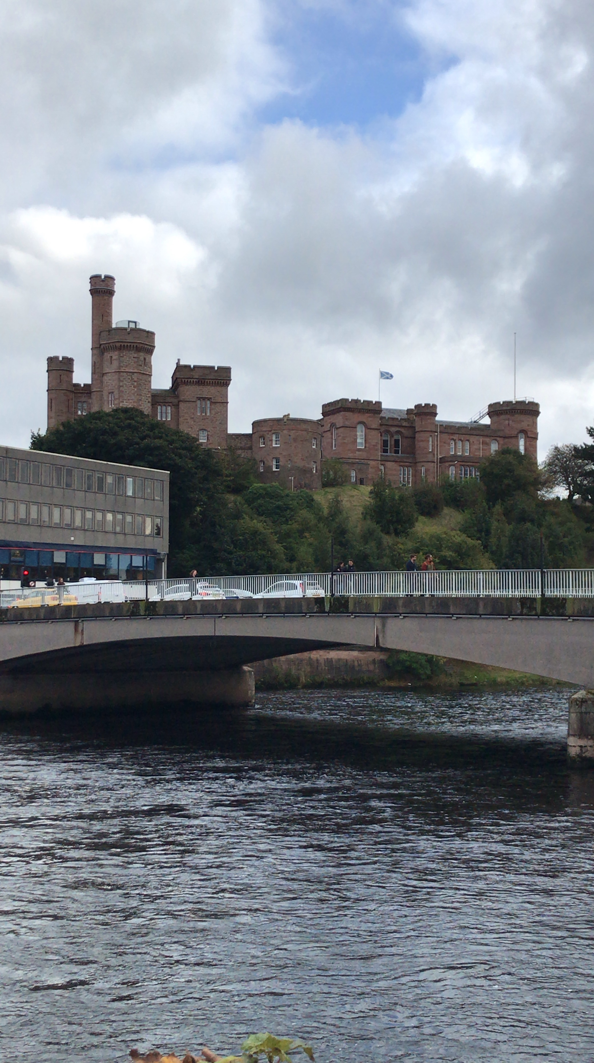 red brick castle above a bridge and river