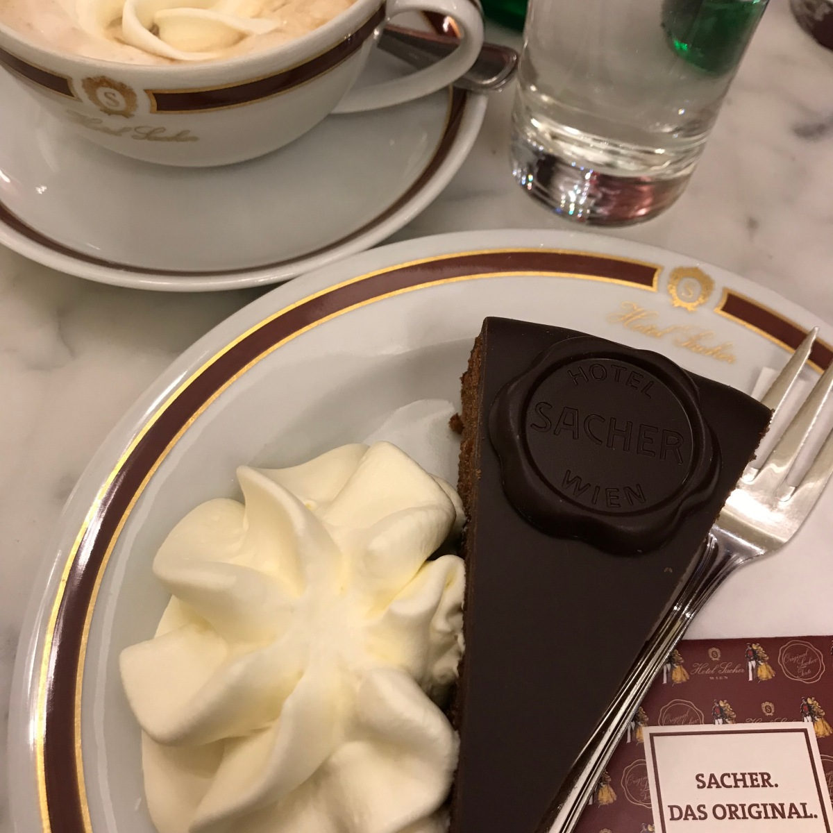 Sachertorte chocolate cake with whipped cream at Hotel Sacher in Vienna