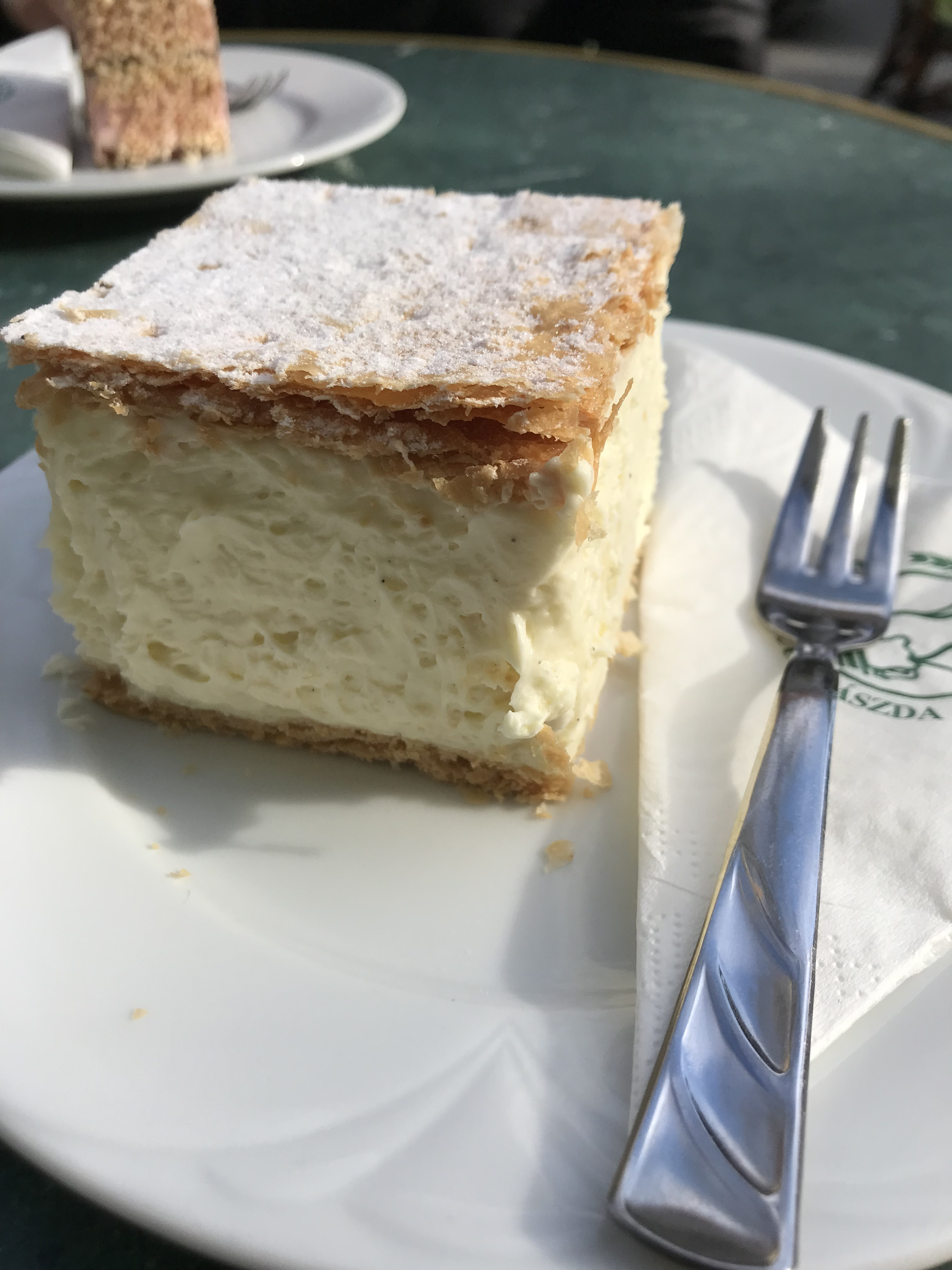 White pastry cream between thin layers of flaky puff pastry on a plate next to a fork