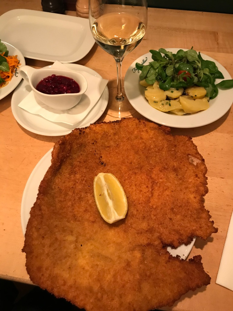 Large schnitzel with lemon on a plate next to a glass of white wine and potato salad
