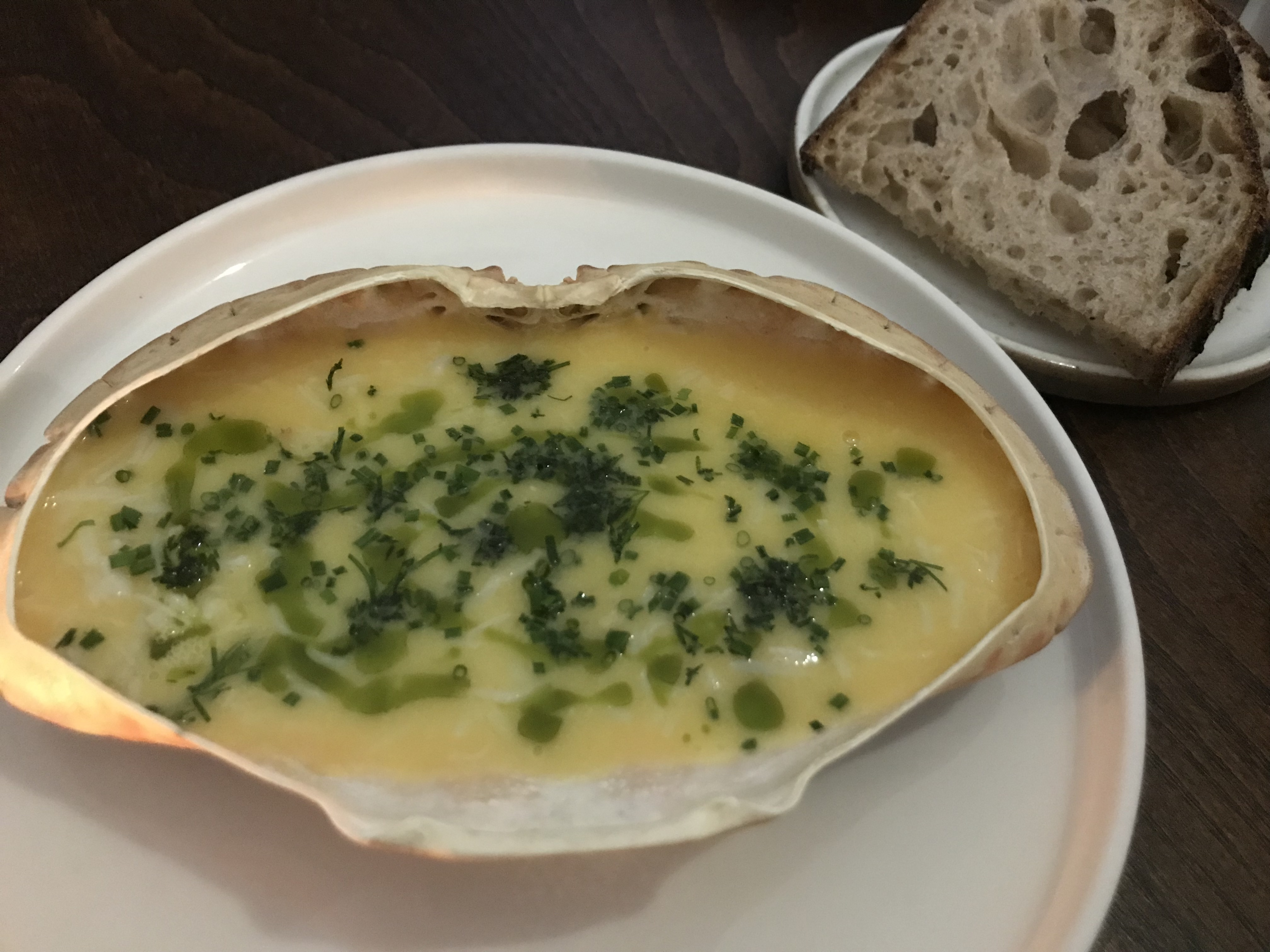 crab shell filled with butter topped with green herbs with plate of bread next to it