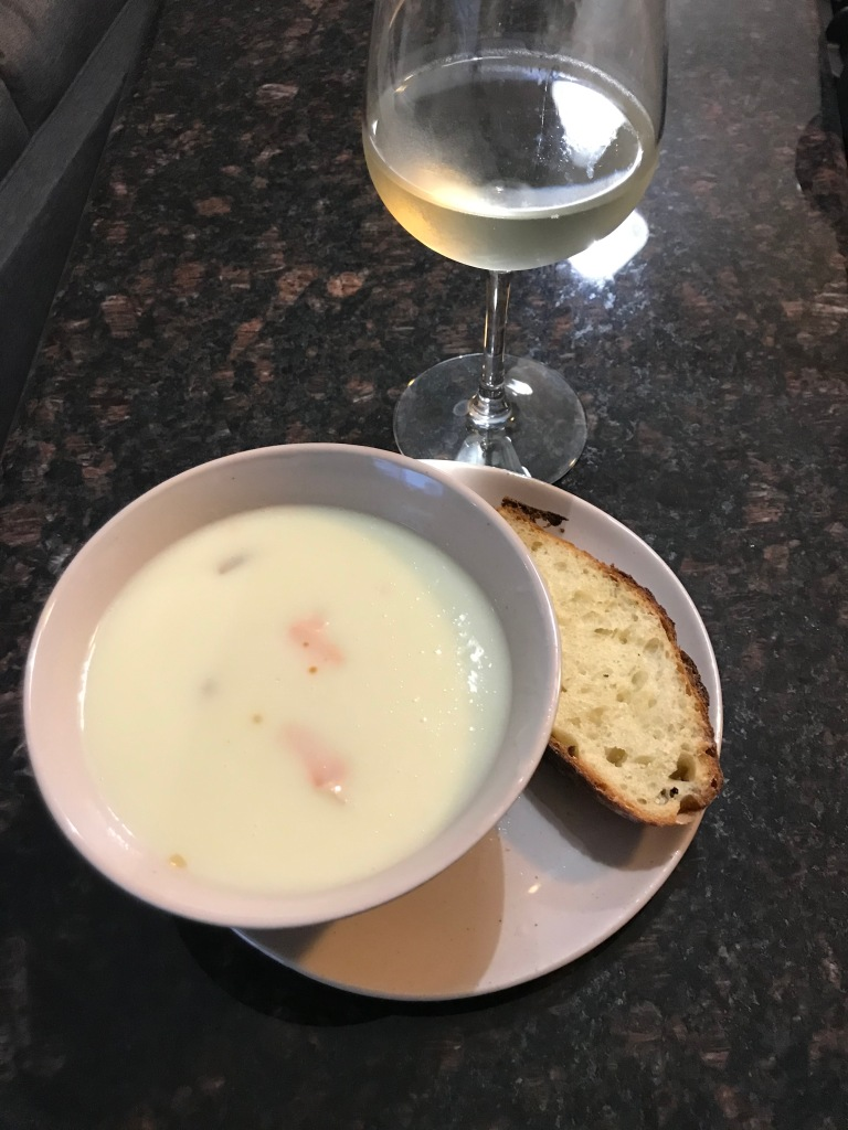 potato soup and slice on bread on plate next to wine glass