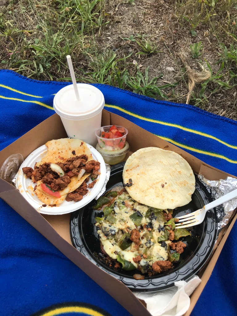Tacos and drink with a straw on a blanket